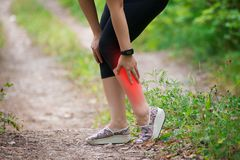 Faccia soffrire nello stinco del ` s della donna, massaggio della gamba femminile, lesione mentre corrono, trauma durante l'allen Fotografie Stock