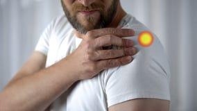 Faccia soffrire in spalla indicata con il punto, giunto danneggiato uomo dopo l'esercizio fisico fotografia stock