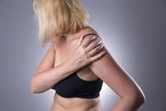 Faccia soffrire in spalla, la cura delle mani femminili, dolore nel corpo del ` s della donna Fotografie Stock