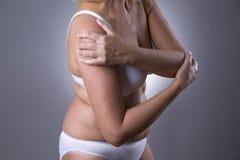 Faccia soffrire in spalla, la cura delle mani femminili, dolore nel corpo del ` s della donna Fotografia Stock