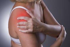 Faccia soffrire in spalla, la cura delle mani femminili, dolore nel corpo del ` s della donna Fotografie Stock Libere da Diritti