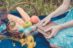 Faccia un picnic in natura all'estate, canestro con alimento Giovane donna con la a Immagini Stock