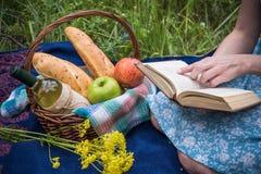 Faccia un picnic in natura all'estate, canestro con alimento Giovane donna con la a Fotografia Stock
