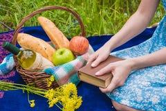 Faccia un picnic in natura all'estate, canestro con alimento Giovane donna con la a Fotografie Stock