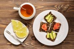 Faccia un spuntino con il pesce e l'avocado rossi sui cracker della segale Tè con il limone Priorità bassa rustica di legno fotografie stock libere da diritti