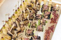 Faccia un spuntino su un vassoio, spiedi con formaggio, la melanzana, le patate, uva Fotografia Stock