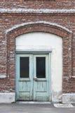 Facciata antica del mattone con le porte verdi Entra del magazzino di vecchio stile Immagine Stock Libera da Diritti