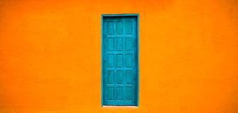 Facciata arancio luminosa viva di colore con a porta chiusa blu-verde nel centro di grande ampio fondo arancio vuoto di struttura Immagine Stock Libera da Diritti