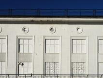 Facciata bianca della casa con un ferro battuto che gratta su una serie di finestre immaginarie Fotografie Stock Libere da Diritti