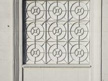 Facciata bianca della casa con un ferro battuto che gratta sulla finestra Fotografia Stock Libera da Diritti
