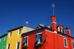 Facciata colorata dell'isola di Burano nei precedenti del blu Immagini Stock