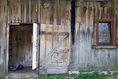Facciata con la vecchia casa rurale di legno della porta aperta fotografie stock libere da diritti