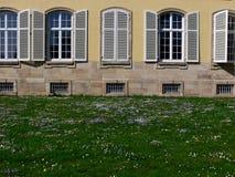 Facciata del castello con le finestre e gli otturatori semicircolari dietro il prato del fiore fotografie stock libere da diritti