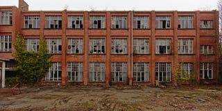 Facciata del muro di mattoni con le finestre rotte di una scuola abbandonata Fotografie Stock