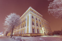 Facciata dell'edificio scolastico di vecchia scuola Paesaggio di inverno notte Immagine Stock