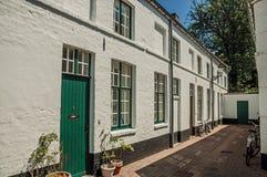 Facciata della casa con mattoni a vista con la porta e delle finestre in un piccolo vicolo a Bruges Fotografia Stock Libera da Diritti