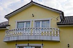 Facciata della costruzione con un balcone e le finestre Fotografie Stock
