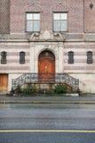 Facciata della larghezza della costruzione di mattone una porta di legno e un portico Fotografia Stock