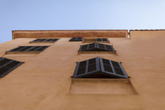 Facciata delle case spagnole Mediterranee beige contro un chiaro cielo blu Immagini Stock Libere da Diritti
