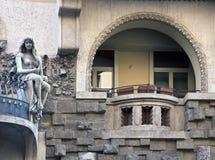Facciata di stile Liberty con la statua della giovane donna che si siede su un ostacolo Immagine Stock