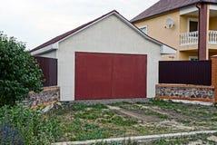Facciata di un garage privato con i portoni rossi Fotografie Stock Libere da Diritti
