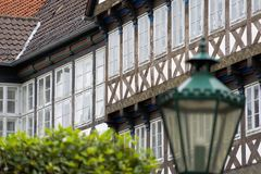 Facciata di una casa a graticcio in una vecchia città, con una lanterna deliberatamente vaga e una corona vaga degli alberi nella immagini stock