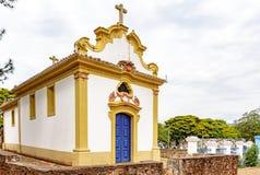Facciata di una chiesa storica nell'architettura coloniale con il cimitero antico dietro immagine stock libera da diritti