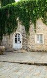 Facciata di vecchia casa invasa con l'edera Finestra e porta Vecchia città di Budua montenegro fotografia stock libera da diritti