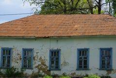 Facciata di vecchia casa rurale grigia con le finestre blu fotografie stock