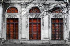 Facciata di vecchia costruzione abbandonata con tre grandi finestre incurvate del vetro rosso Fondo monocromatico Fotografia Stock