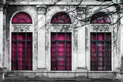 Facciata di vecchia costruzione abbandonata con tre grandi finestre incurvate di vetro rosa Fondo monocromatico fotografia stock