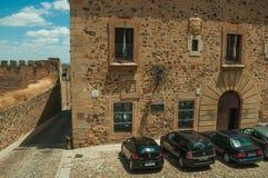 Facciata di vecchia costruzione davanti al piccolo quadrato con le automobili parcheggiate a Caceres fotografia stock libera da diritti