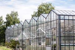 Facciata di vetro della serra in giardino contro il cielo nuvoloso Fotografia Stock Libera da Diritti