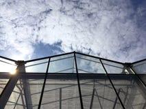 Facciata di vetro della serra industriale contro il cielo nuvoloso Immagini Stock