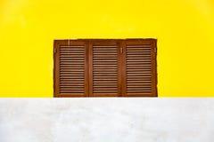 Facciata gialla e una finestra di legno Immagine Stock