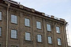 Facciata grigia di vecchio grattacielo con le finestre sui precedenti del cielo Fotografie Stock