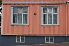 Facciata islandese tipica della casa nel colore di rosa di color salmone fatto di ferro ondulato e con le finestre di legno bianc Immagine Stock Libera da Diritti