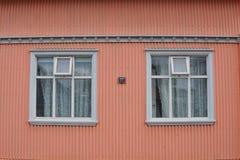 Facciata islandese tipica della casa nel colore di rosa di color salmone fatto di ferro ondulato e con le finestre di legno bianc Immagine Stock