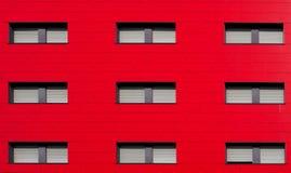 , Facciata rossa luminosa di un edificio residenziale moderno con gli otturatori grigi immagini stock