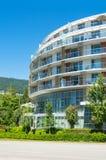 Facciata rotonda di edificio residenziale con il fondo del cielo blu e della montagna immagine stock libera da diritti