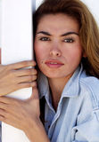 Face 199. Close up headshot of Latina Woman leaning against a white post Stock Image