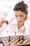 Face. Young businesswoman playing chess, nice face stock photo