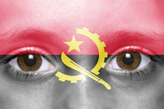 Face with angolan flag. Human`s face with angolan flag Stock Photo