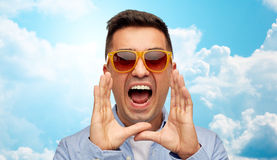 Face of angry shouting man in shirt and sunglasses. Summer, emotions, communication and people concept - face of angry middle aged latin man in shirt and Stock Image