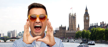Face of angry shouting man in shirt and sunglasses. Travel, tourism, emotions, communication and people concept - face of angry middle aged latin man in shirt Royalty Free Stock Photo