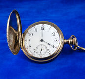 Face of Antique Gold Pocket Watch. With cover open to display time.  Gold watch is displayed against deep blue velvet for a rich look Royalty Free Stock Photos