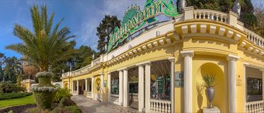 Entrance colonnade of the Arboretum. Sochi, Russia. The face of the Arboretum is the entrance with lawn and palm tree. Beautiful building attracts residents and Stock Photography