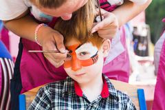 Child boy face painting, making tiger eyes process Royalty Free Stock Photography