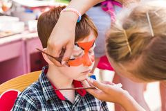 Child boy face painting, making tiger eyes process Royalty Free Stock Photos