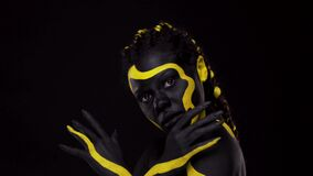 Face art. Dancing woman with black and yellow body paint. Young african girl with colorful bodypaint. An amazing afro